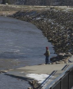 An eager fisherman is undeterred by high water and swift current